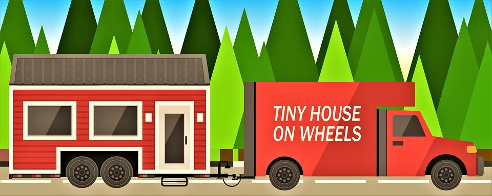Majhna hiška na kolesih, ki jo vleče kombi.