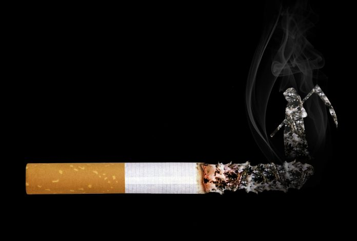 Cigareta do polovice izgorela na črnem ozadju