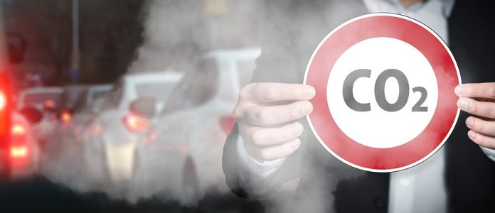 Roke držijo znak za omejitev izpustov, v ozadju avtomobili in izpusti