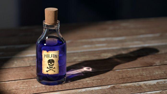 Steklenička strupa na leseni mizi
