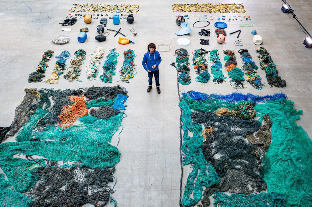 Morski odpadki urejeno ležijo na tleh, poleg stoji ustanovitelj podjetja
