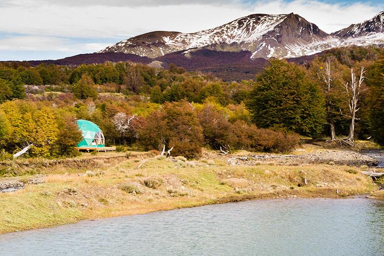 Majhen kupolast apartma ob jezeru, sredi divjine, v ozadju gore