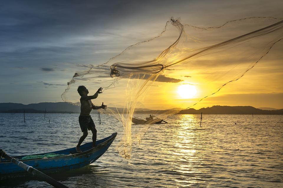 Ribič stoji na čolnu, v zrak je vrgel ribiško mrežo