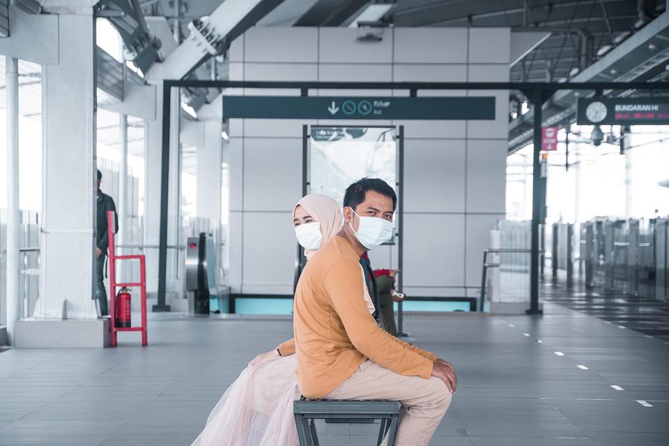 Moški in ženska sedita na klopci na železniški postaji