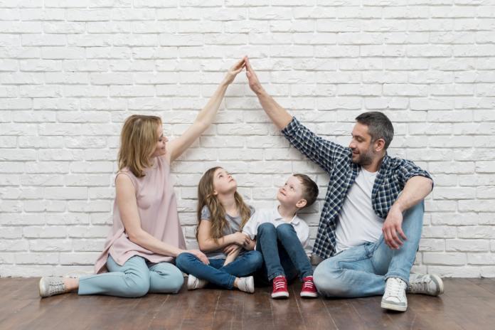 mlada družina sedi ob zidu, starša imata sklenjeni roki (naredila sta streho)