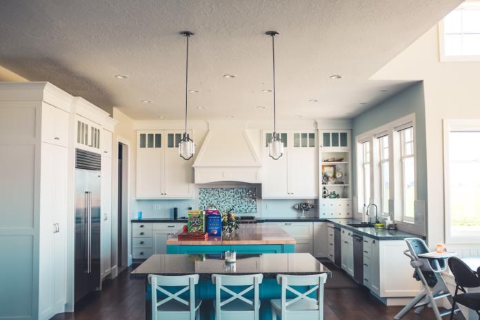 Pogled na kuhinjo, ki jo popestri modra barva in barvita kuhinjska obloga
