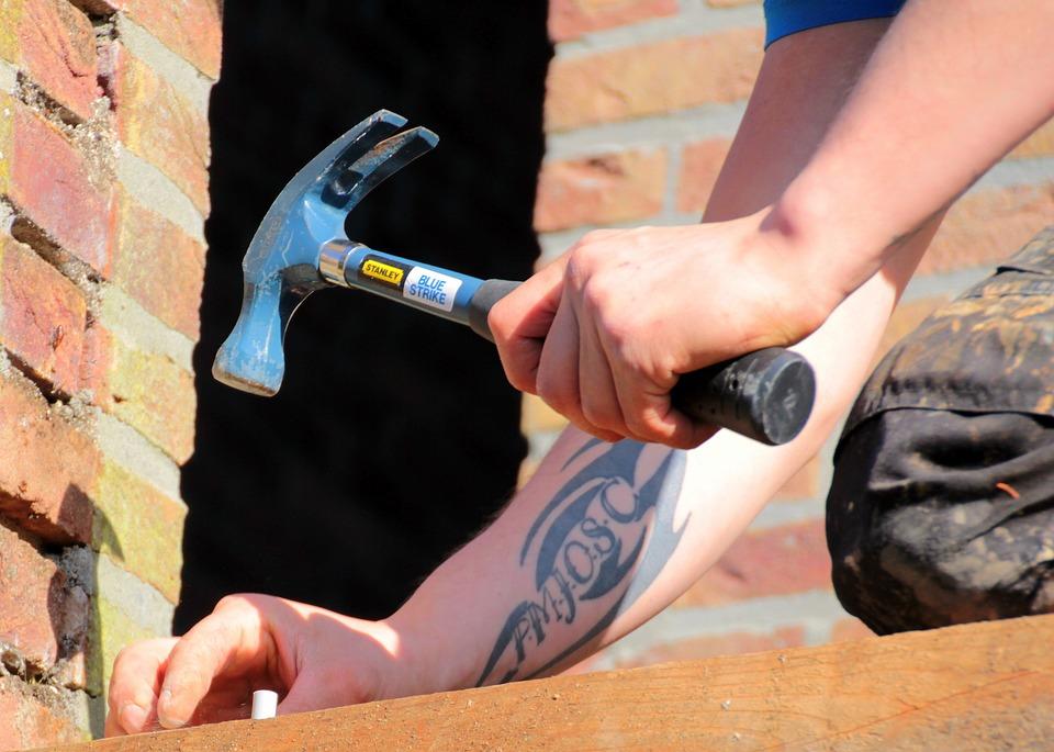 Roka drži kladivo in vijak