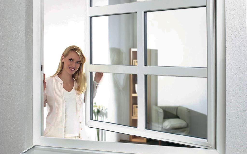 Ženska z roko drži odprto okno in se smeji