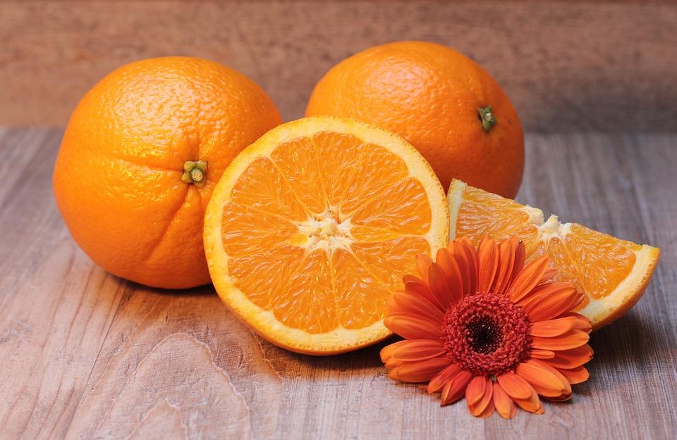 Tri pomaranče, dve sta celi, ena pa narezana na pol, zraven je cvetlica