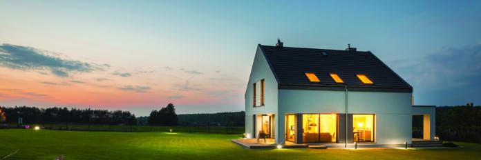 Hiša na travniku osvetljena od znotraj knauf
