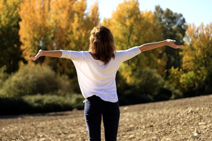Ženska z razprtimi rokami stoji na polju, v ozadju so vidna drevesa