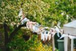 Vrvica z zastavicami plapola v vetru, v ozadju drevo in hiša