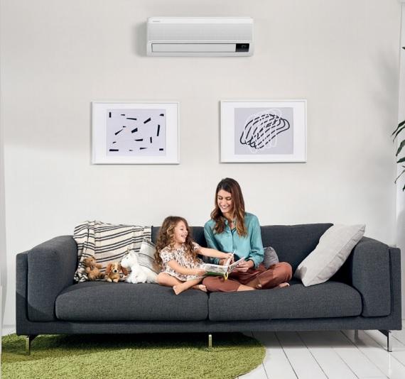 Mama in hčerka sedita na kavču, nad njima je na steni klima