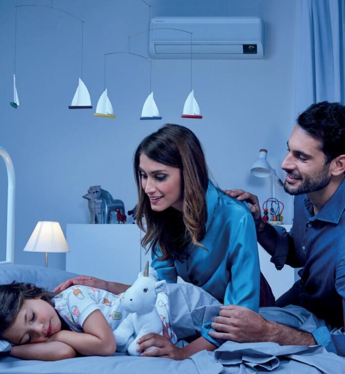 Starša se sklanjata nad spečo deklico, v ozadju na steni visi klima