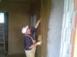 Moški nanaša ilovnate omete na steno