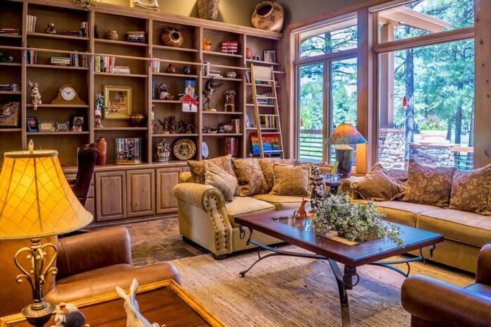 Dnevna soba s knjižnimi policami, stekleno steno, kavčem in mizo